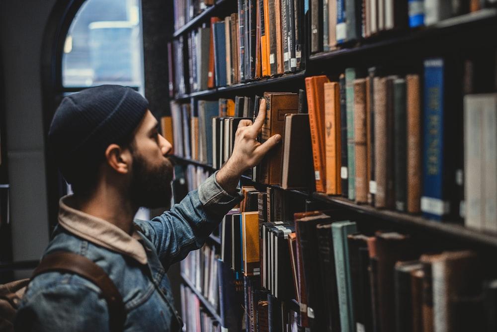 man picking book on bookshelf in library