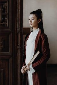 woman wearing brown long cardigan holding book standing near the door