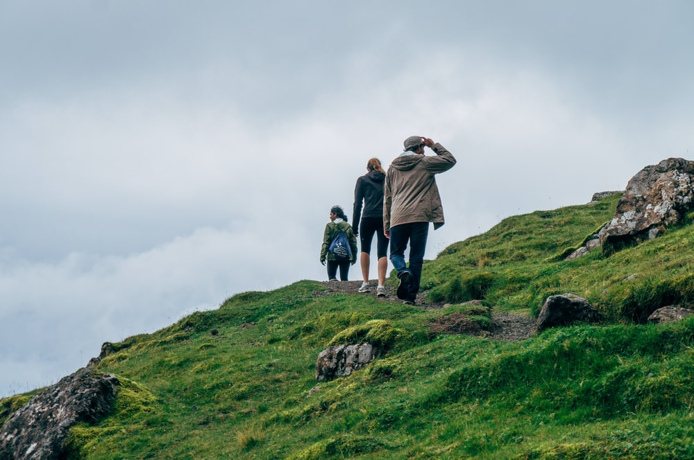 three person walking on green cliff