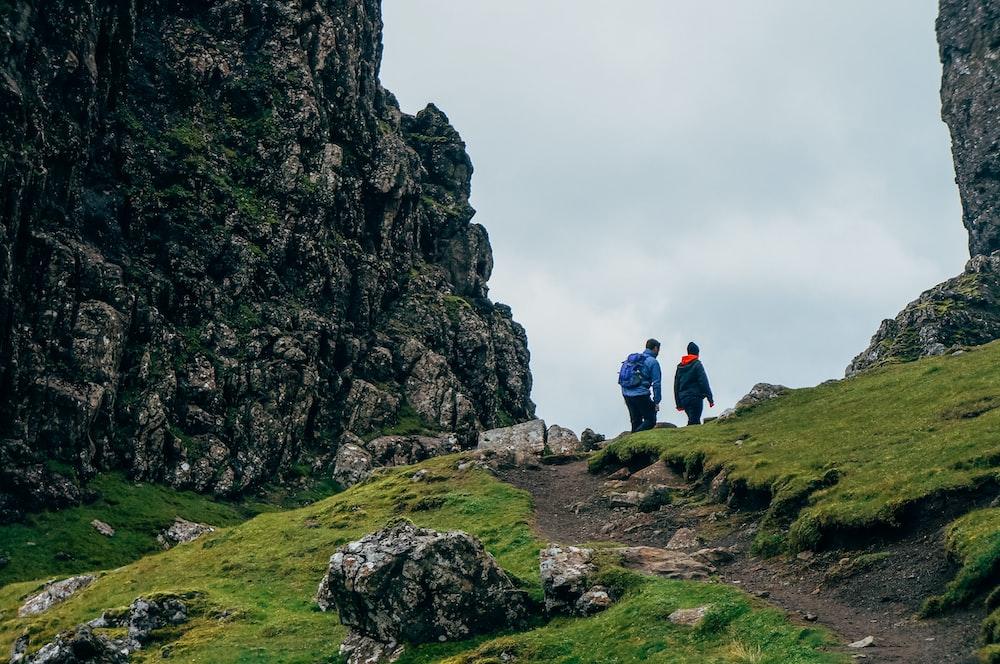 man and woman walking on mountain during daytime