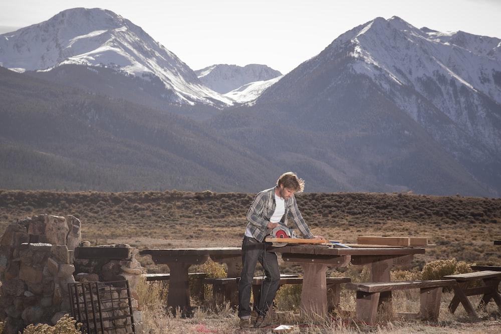 man wearing gray dress shirt standing beside table near brown mountain during daytime
