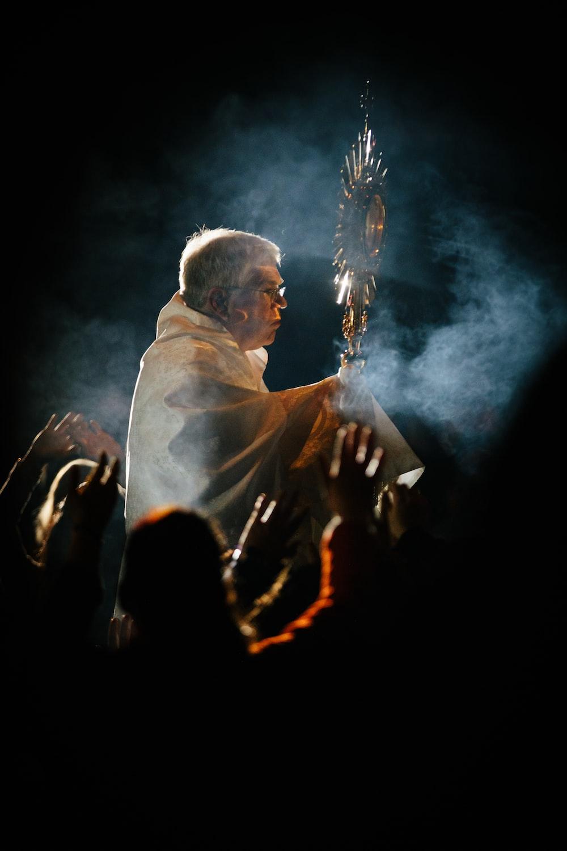 man holding stick wearing white robe