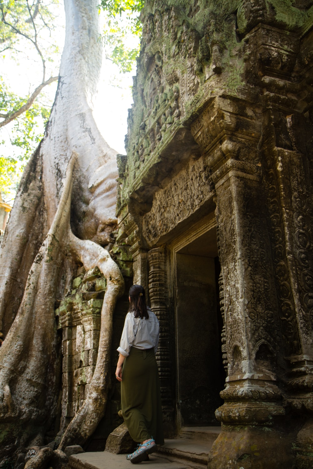 woman standing near concrete door and tree during daytime
