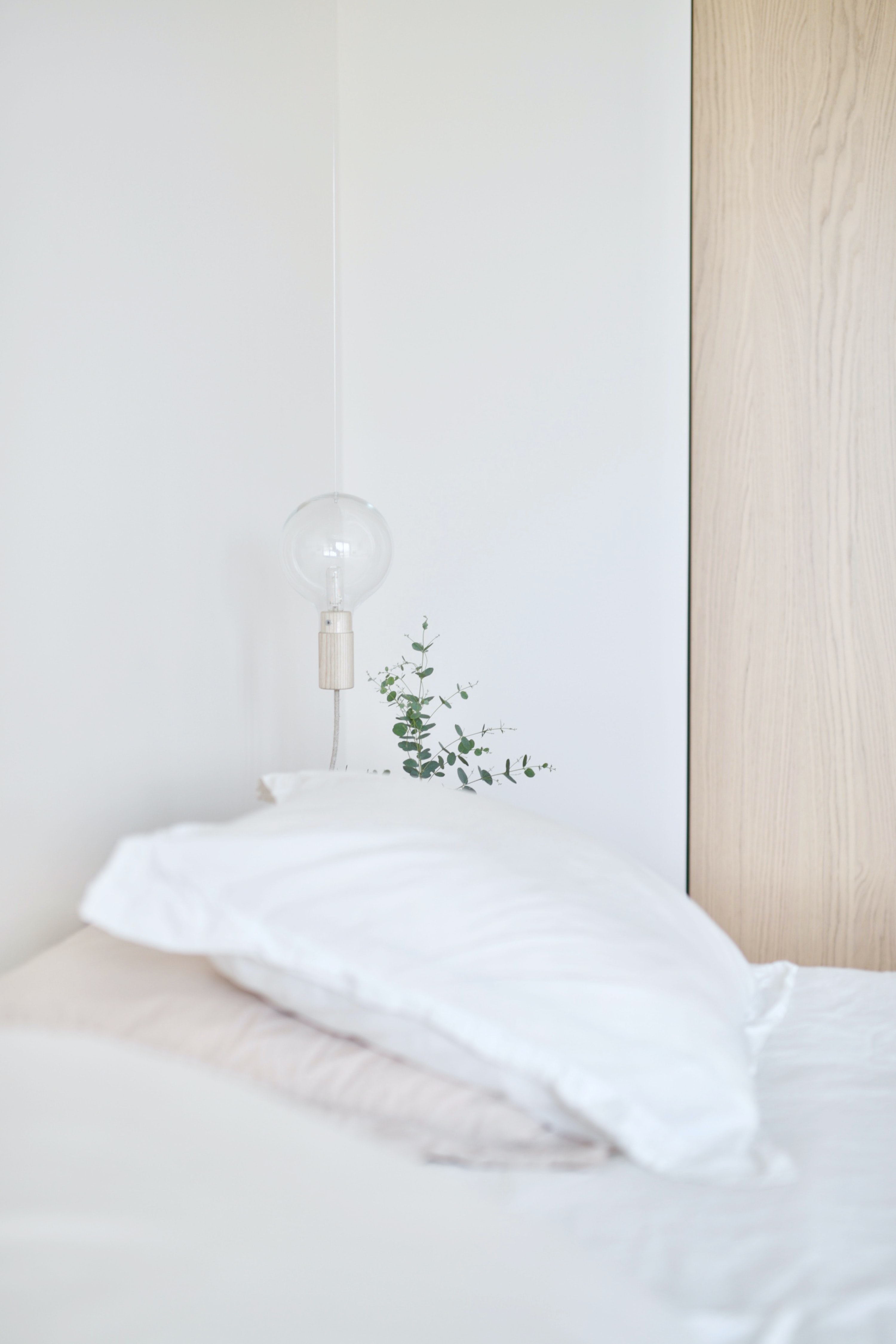 white bed pillow near table lamp
