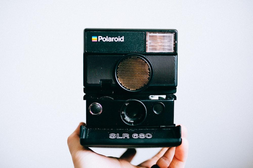 person holding black Polaroid SLR 680 instant camera