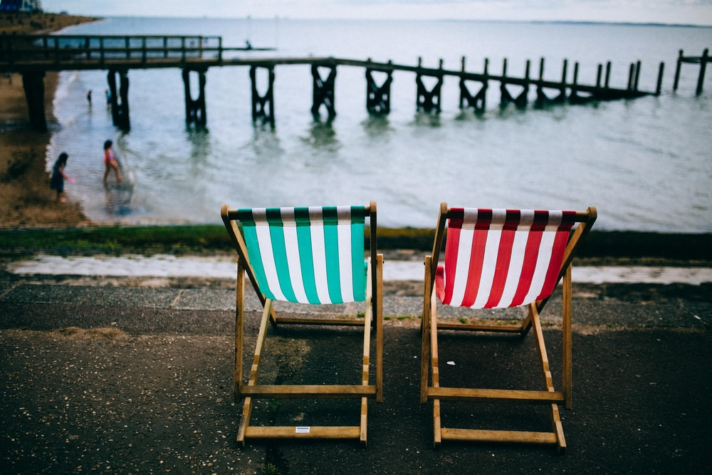 two green, white, and red striped deckchairs near body of water