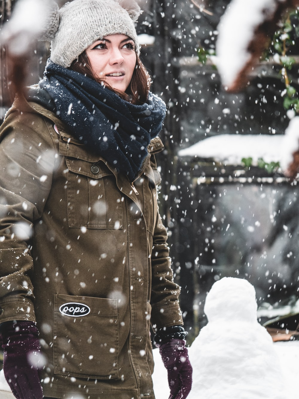 woman standing in field covered with snow and snow dropping down