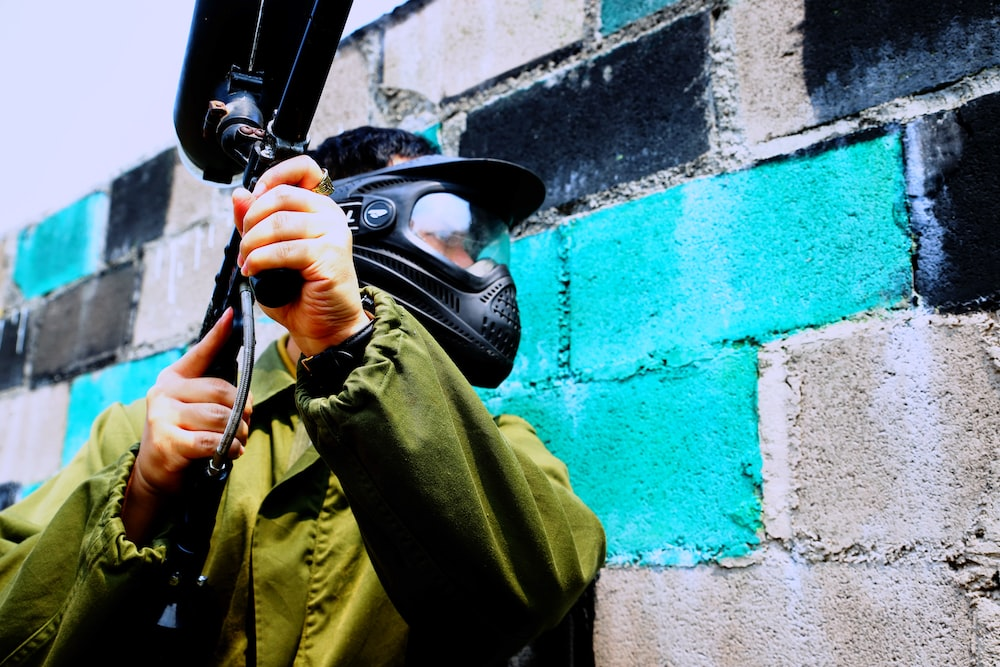 man in green jacket holding paintball gun