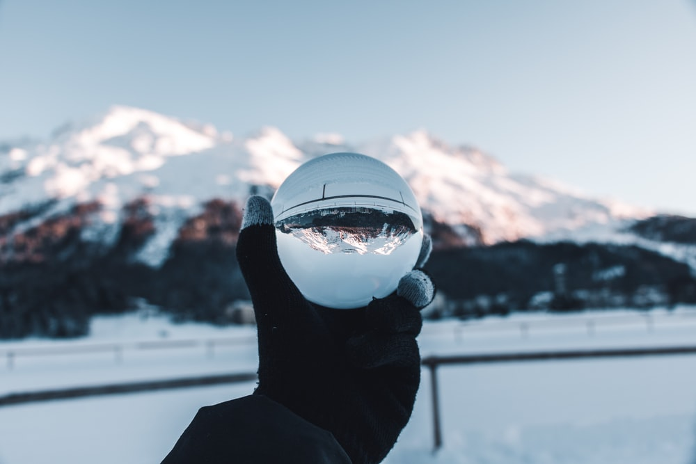 person holding glass crystal ball below snow-covered mountains during daytime