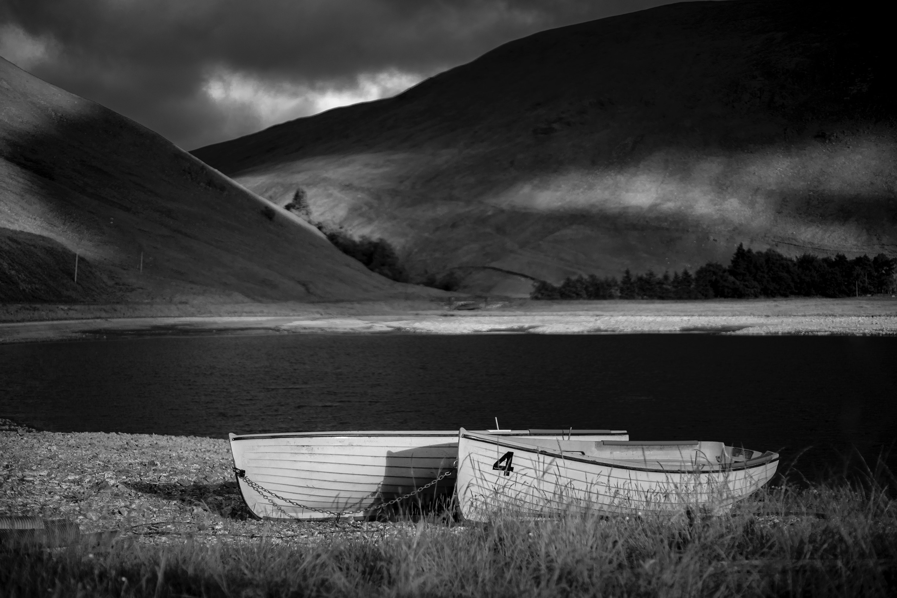 grayscale photography of jon boat on seashore