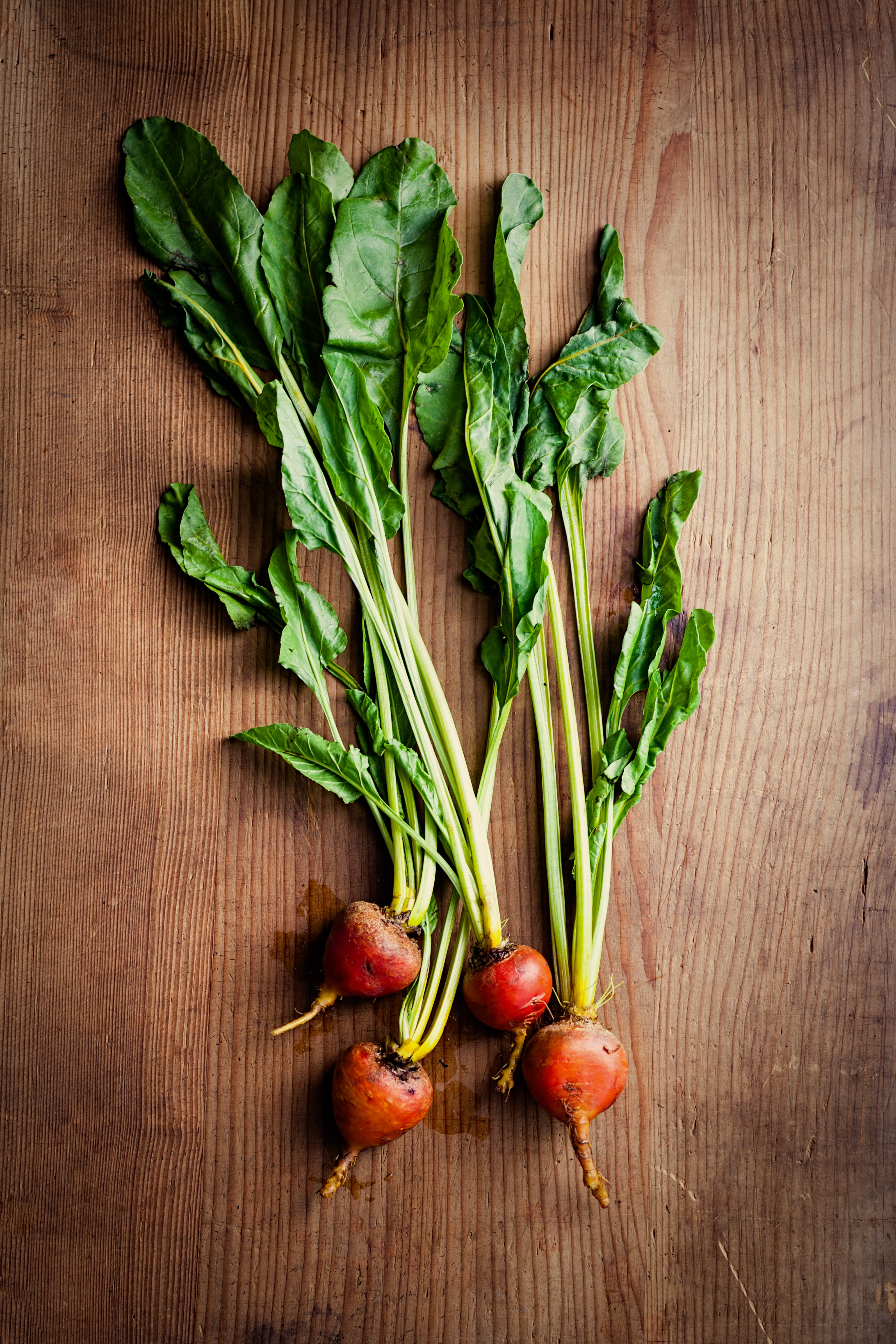 green and red vegetable on brown surface