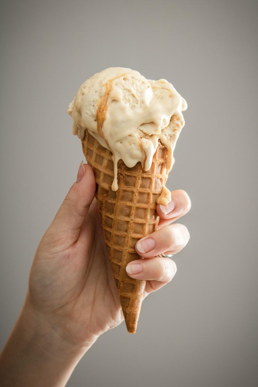 white ice cream on brown cone