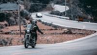 man riding black touring motorcycle during daytime
