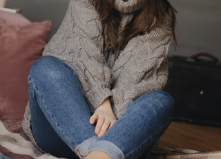 woman sitting on floor wearing gray sweater and blue denim fitted jeans