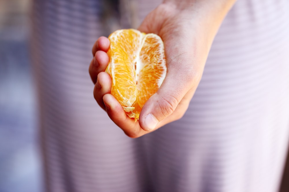 selective focus photography of person squeezing orange fruit