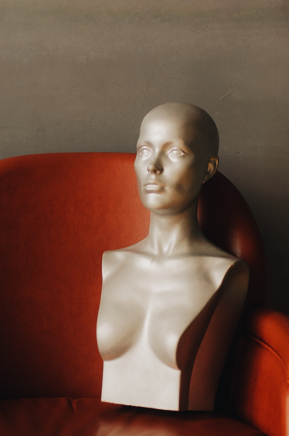 half-body mannequin on red leather chair