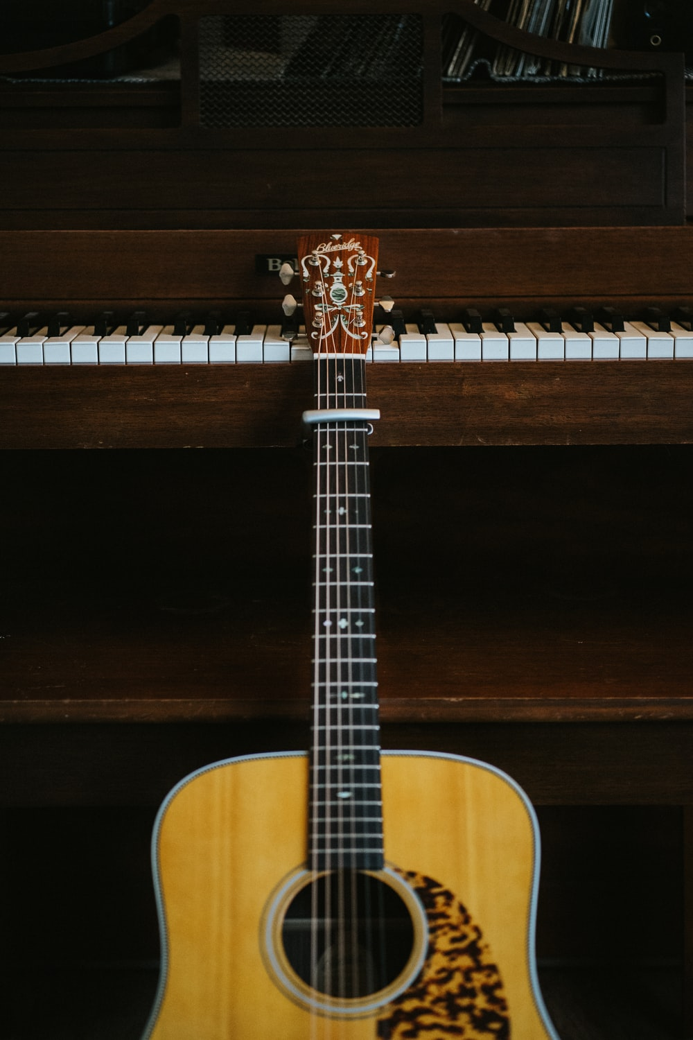 brown acoustic guitar leaning on brown piano
