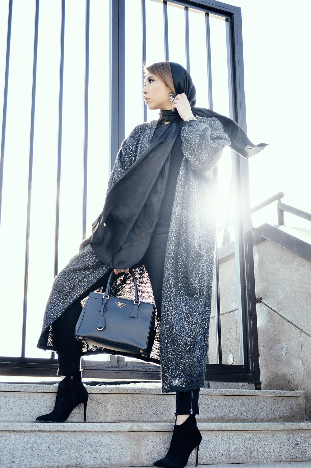 woman in gray coat holding black handbag standing on gray stairs during daytime