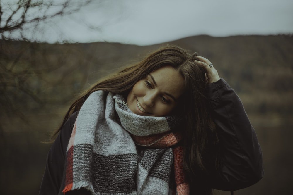 woman wearing gray and red scarf in selective focus photography