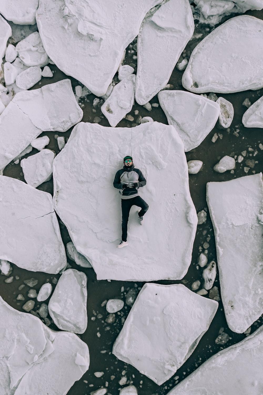 man lying on white rock during daytime