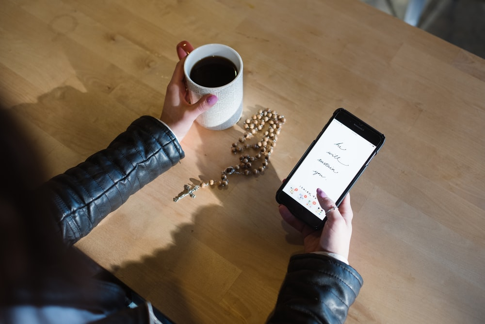 person holding smartphone and mug of coffee
