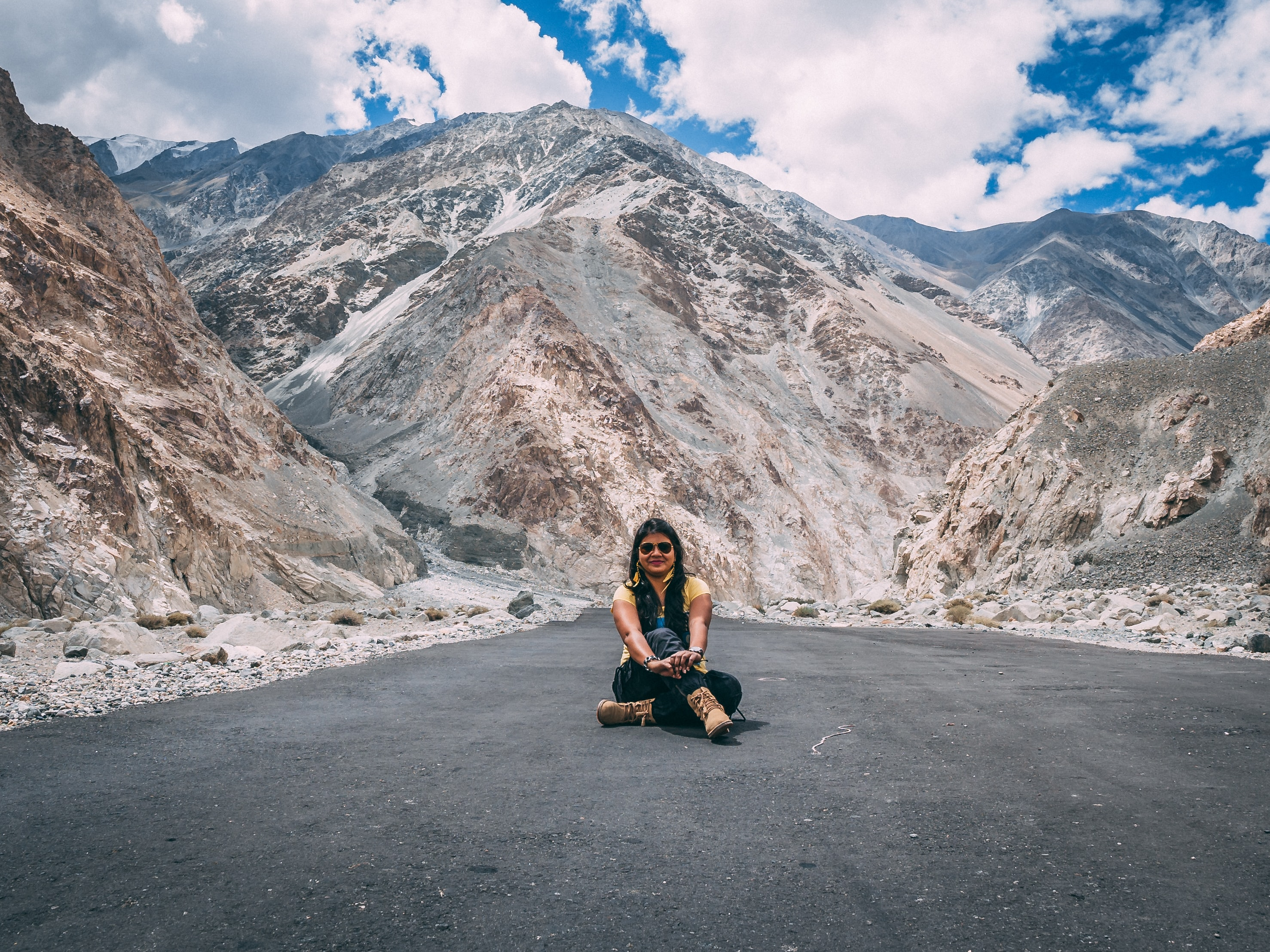woman sitting on road near mountain during daytime