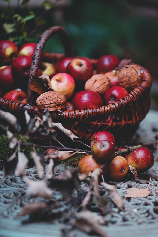 red apple fruits on brown wicker basket