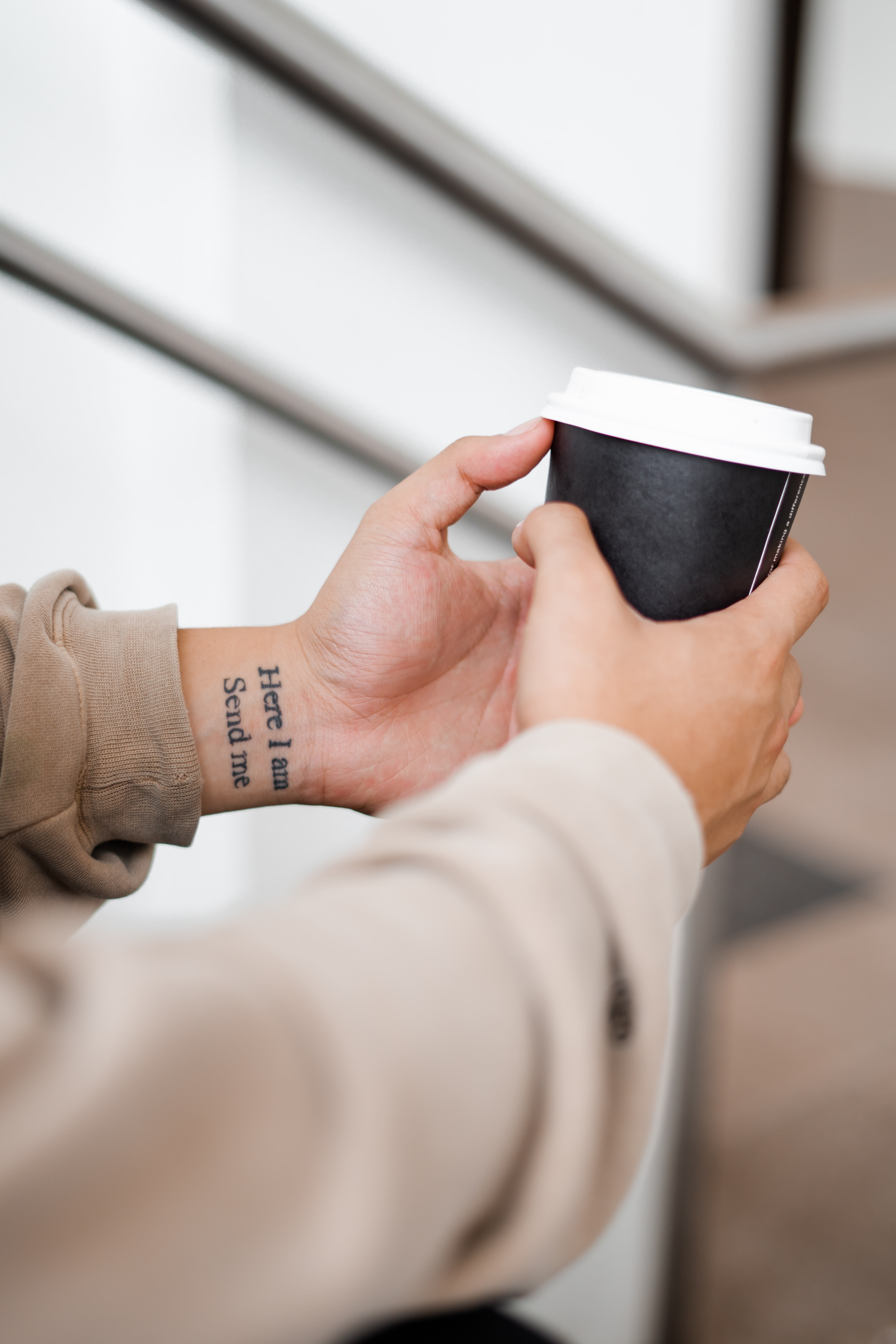 person holding black and white coffee cup