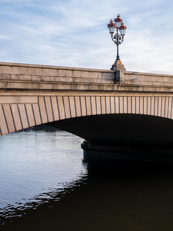 gray concrete bridge across calm water