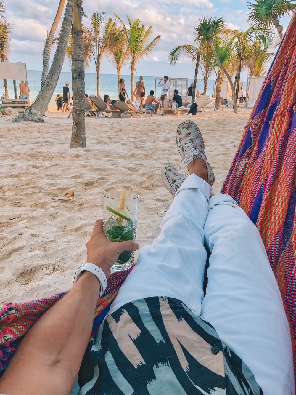 person in white pants lying on blue and red hammock