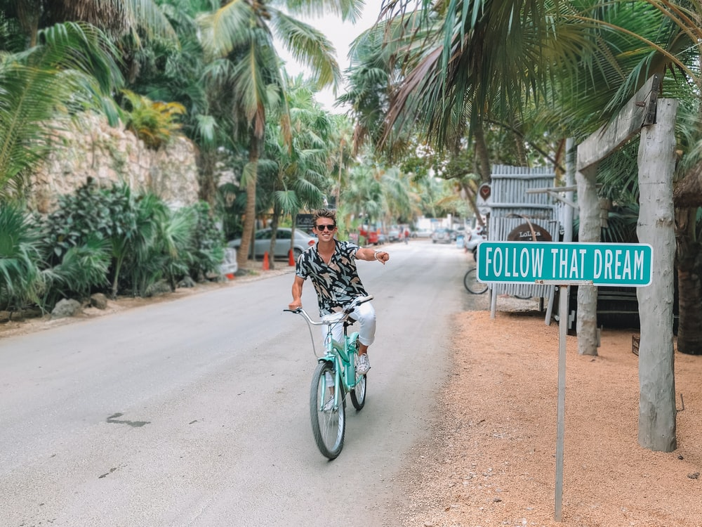 man rides bike pointing to follow that dream signage