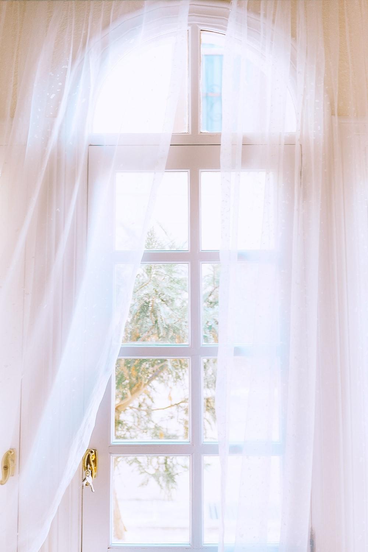 white curtain in white wooden framed window