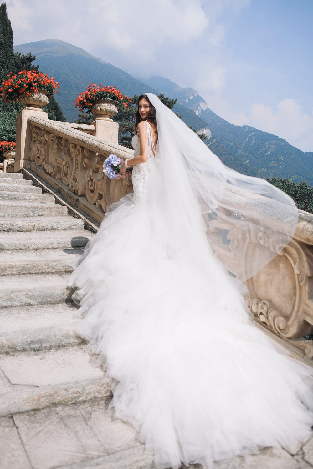 Bridge in white wedding dress walking up stairs with mountains in the background