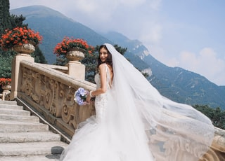 bride holding bouquet standing on white stairs