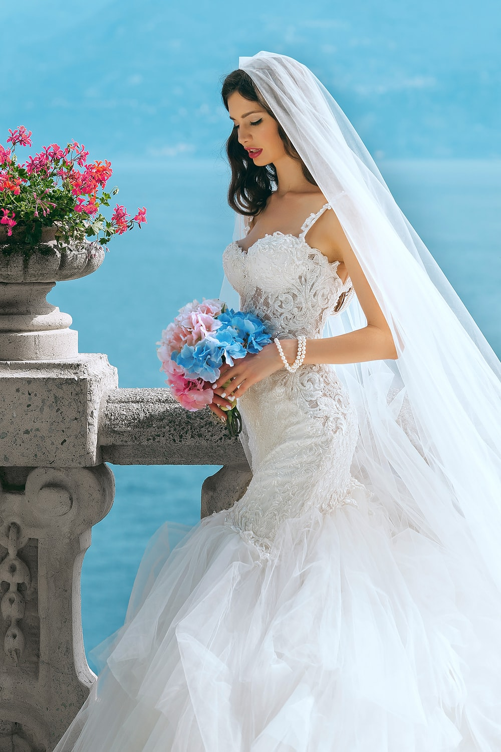 woman in wedding dress while holding flower during daytime