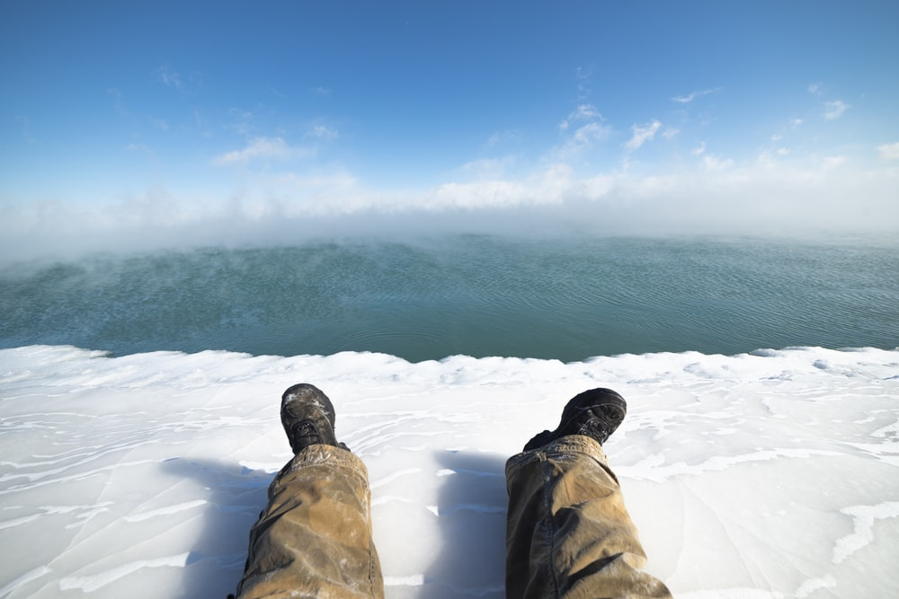 man resting legs on ice
