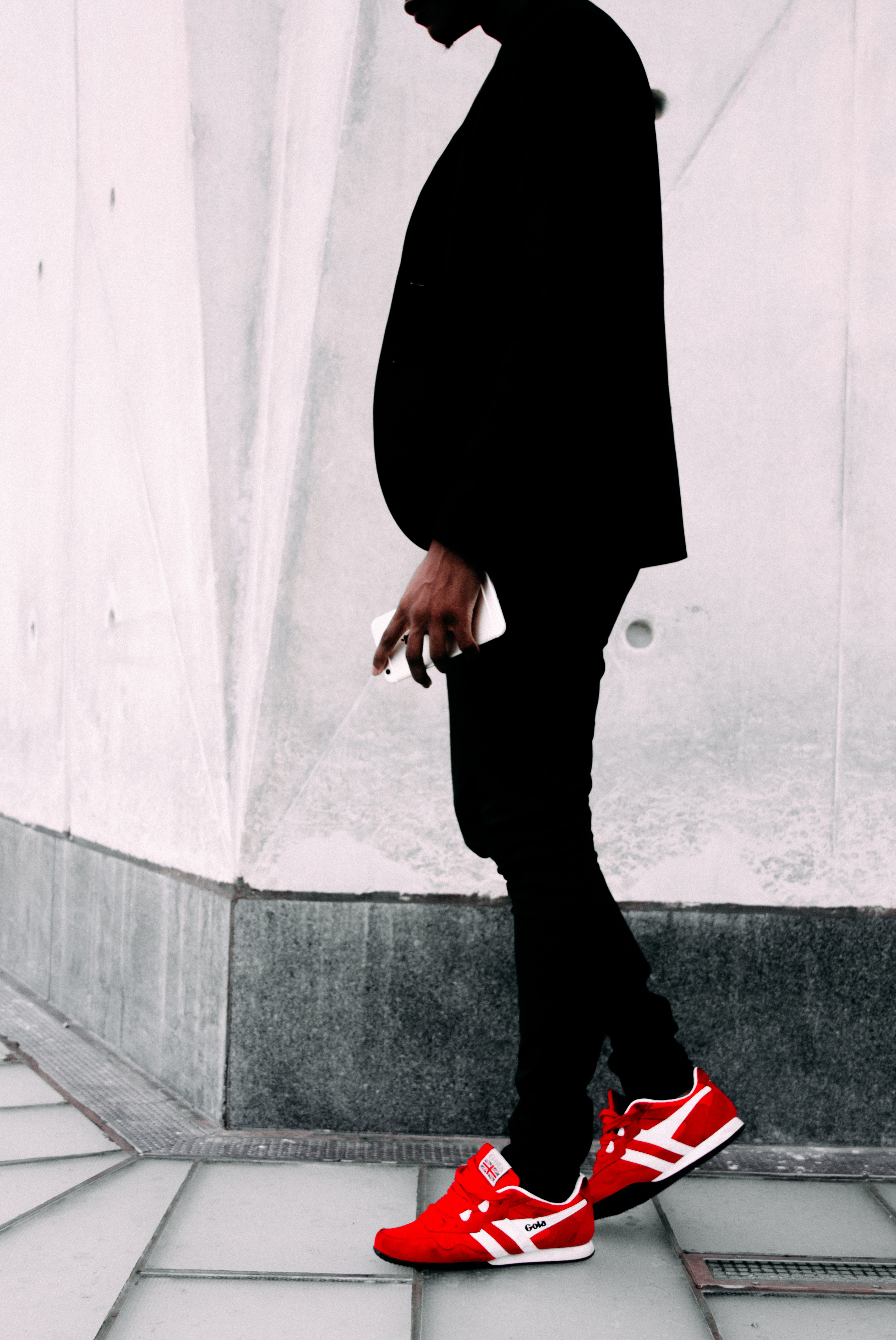 man wearing black suit jacket and red sneakers
