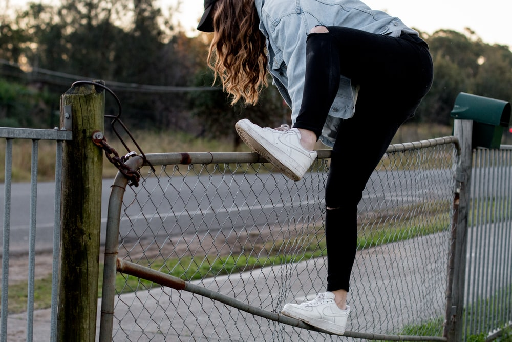 woman climbing over fence