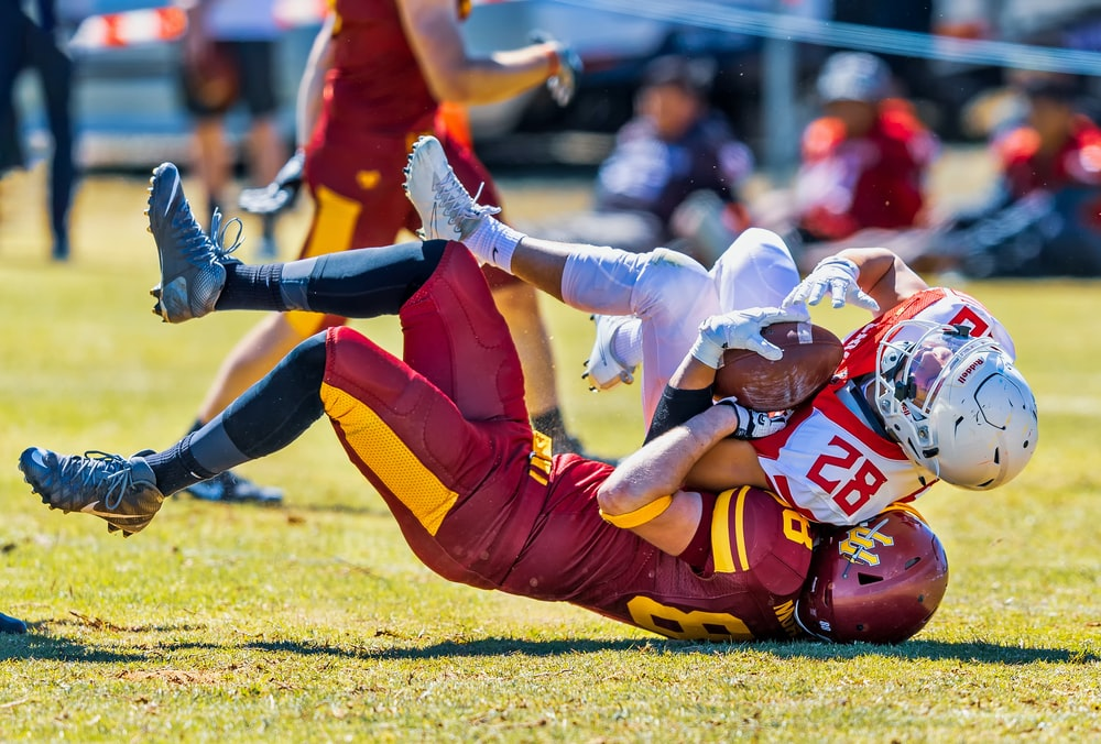 selective focus photography of two football players fighting of the ball during daytime