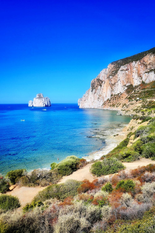 calm sea viewing beach cliff under blue skies