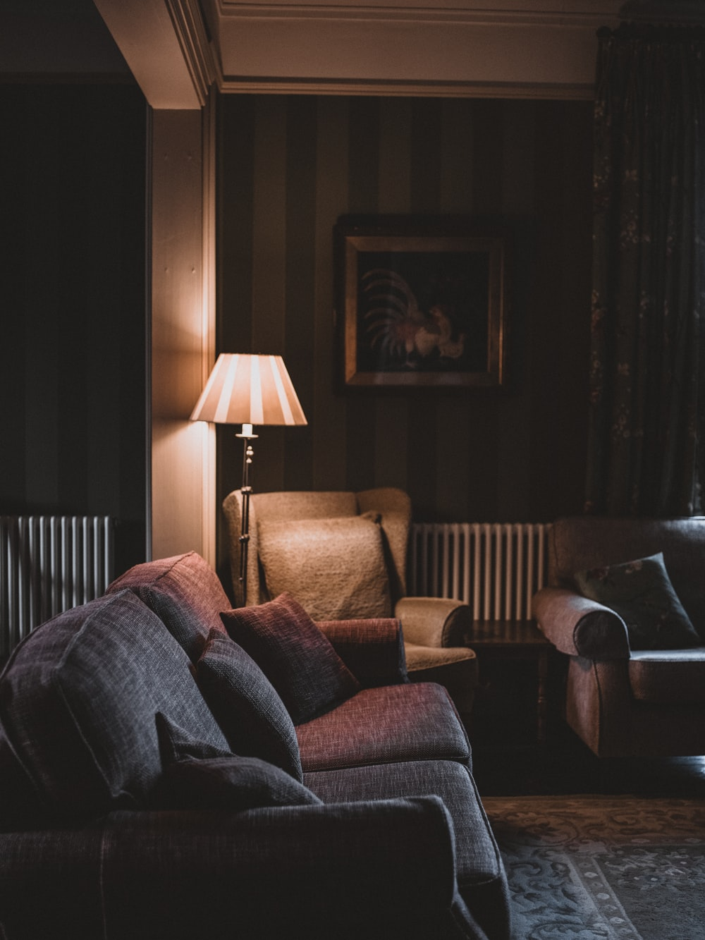 empty gray fabric sofas with turned on floor lamp