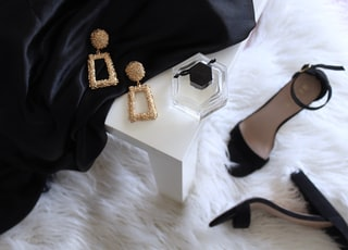 pair of gold-colored earrings on table and black ankle-strap pumps on area rug