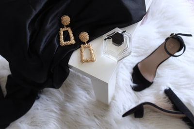pair of gold-colored earrings on table and black ankle-strap pumps on area rug luxury teams background