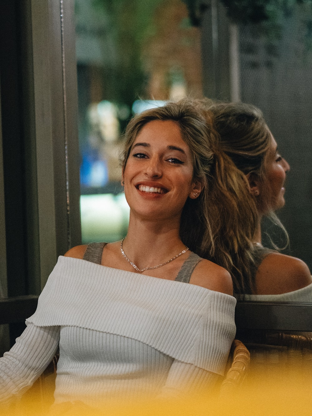 woman in white off-shoulder top leaning on glass wall
