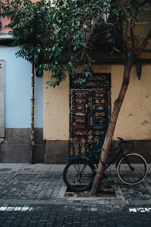 black bicycle beside tree