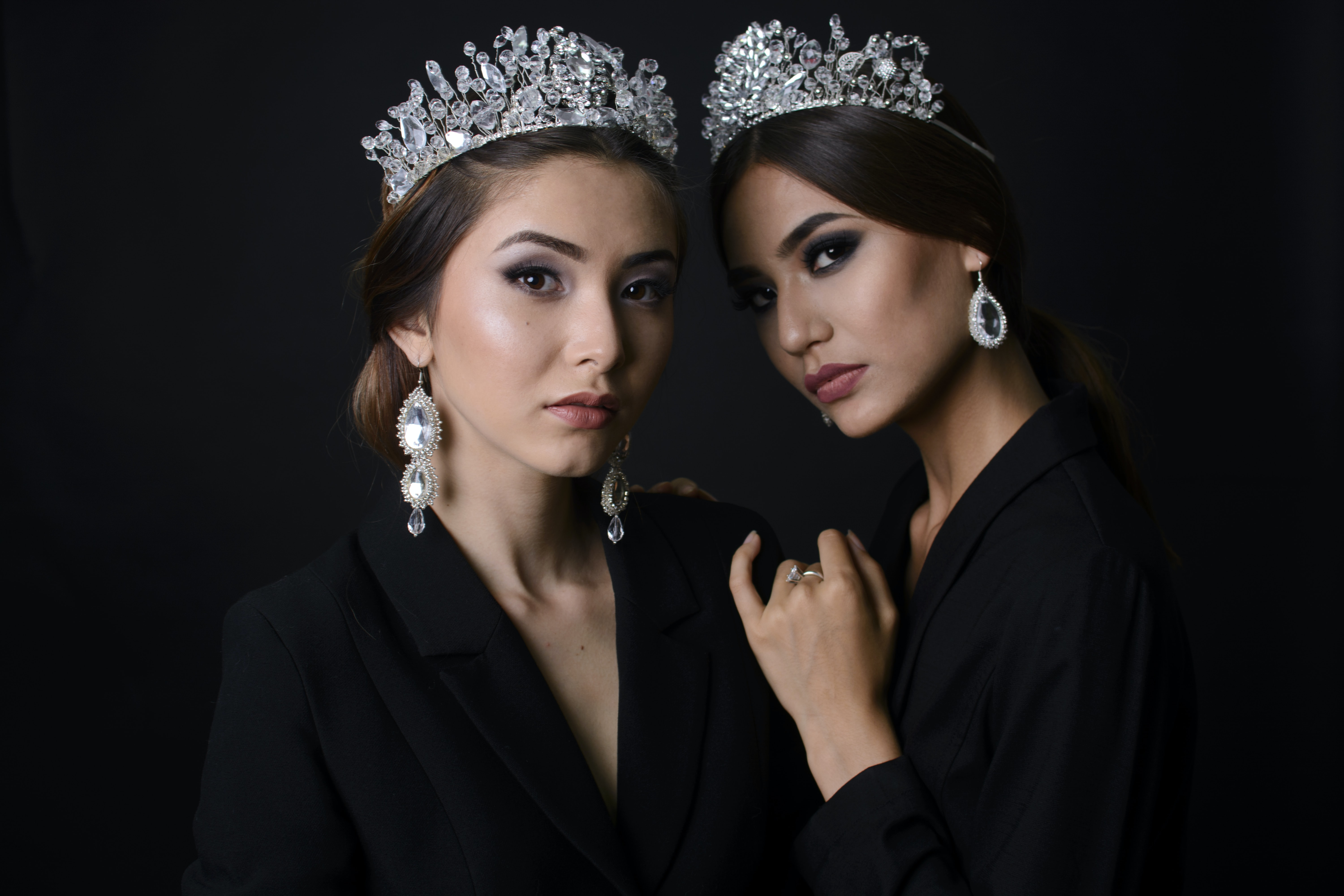 two woman wearing silver-color crowns