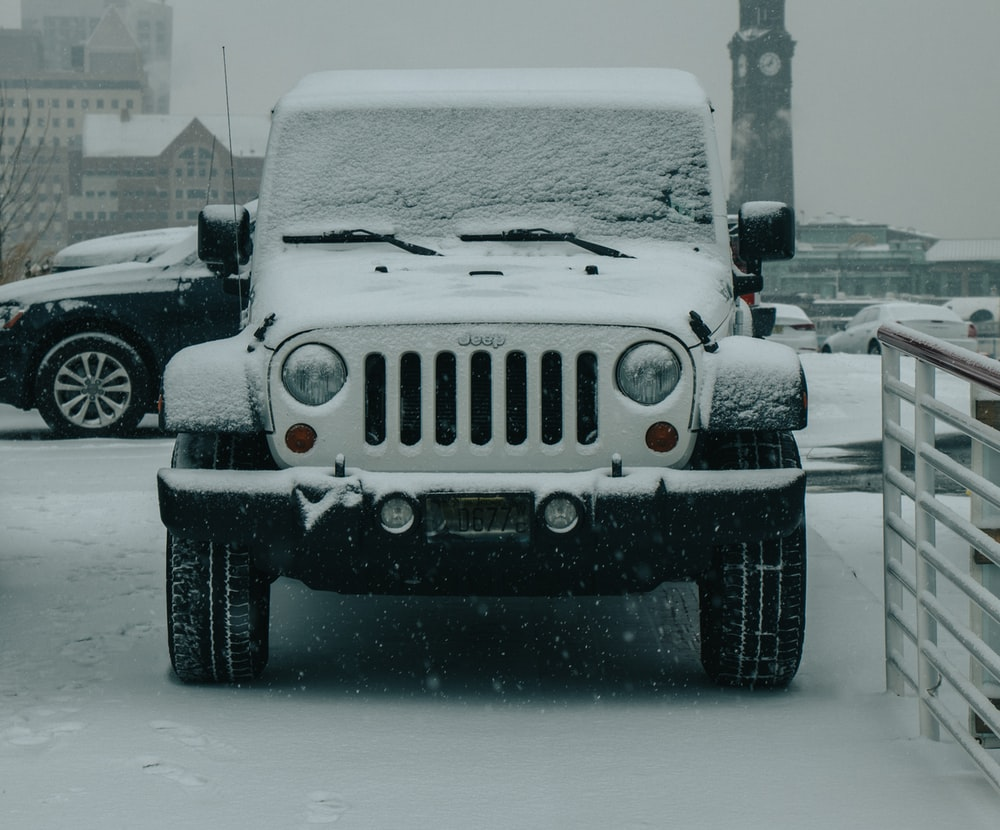 white Jeep Wrangler covered by snow