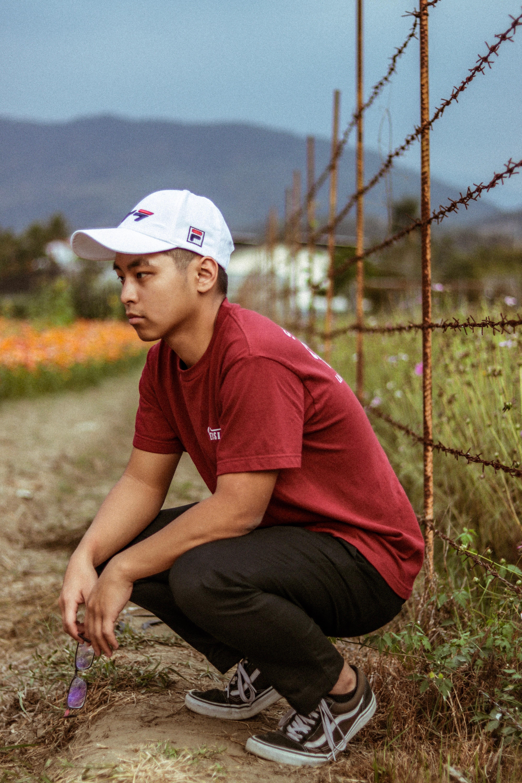 man wearing red shirt sitting beside grass