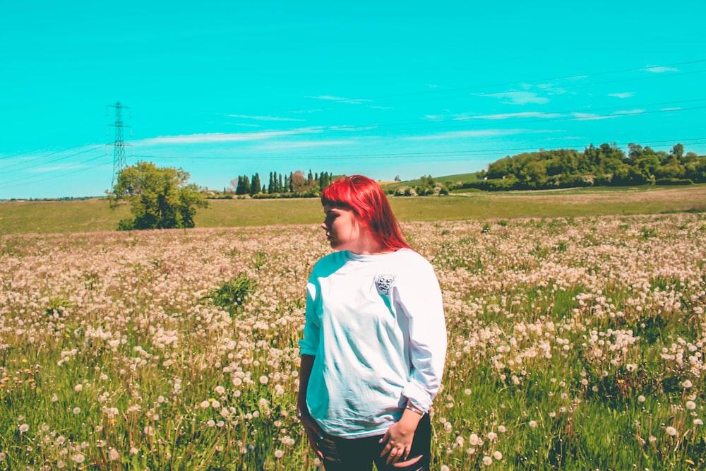 woman wearing sweater standing on flower field