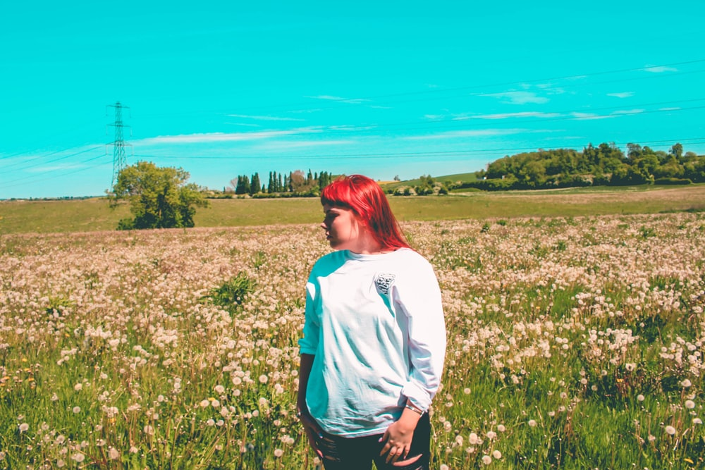 woman wearing sweater standing on flower field